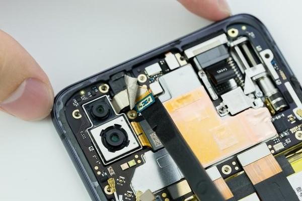 使用镊子,将后置双摄的副摄像头排线上的一张贴纸撕开.